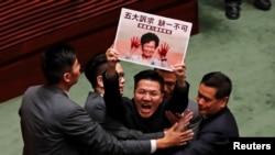 Un legislador prodemocracia es escoltado por agentes de seguridad en la Legislatura el 17 de octubre portando un cartel de la jefa ejecutiva Carrie Lam con las manos manchadas de sangre.