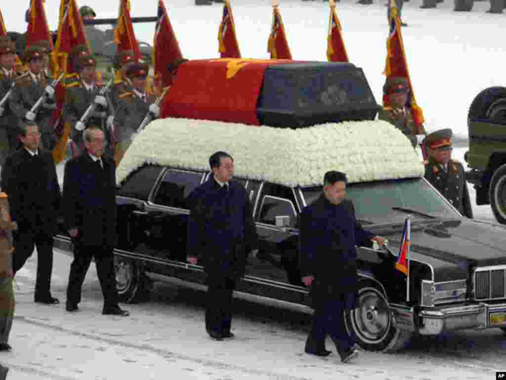 Kim Jong Un, followed by senior party and military officials, accompany the hearse carrying Kim Jong Il. (AP)