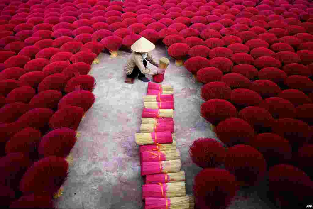 A Vietnamese woman collects incense sticks in a courtyard in the village of Quang Phu Cau on the outskirts of Hanoi.