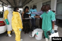FILE - A health worker sprays a colleague with disinfectant during a training session for Congolese health workers to deal with Ebola virus in Kinshasa, Oct. 21, 2014.