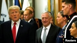 FILE - Secretary of Defense James Mattis, right, escorts U.S. President Donald Trump as he greets military personnel at the Pentagon, July 20, 2017.