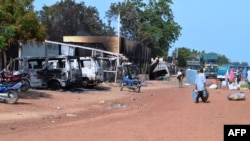People walk past vehicles and shops burnt by Boko Haram Islamists on a street of Benisheik, on Sept. 19, 2013.