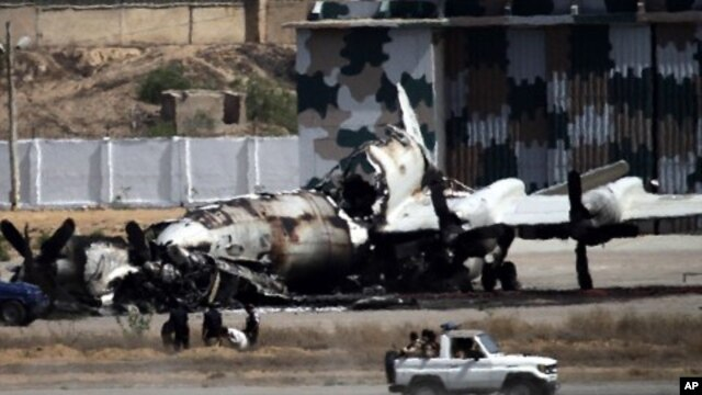 Pakistani troops drive past a wreckage of a gutted aircraft at Pakistan Navy base in Karachi, Pakistan, May 23, 2011