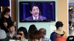 首尔列车站的人群观看日本首相就日本二战投降70周年发表谈话。(2015年8月14日)
