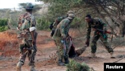 Somali soldiers help a colleague who is wounded by Al-Shabaab gunmen.