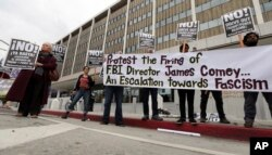 Members of a group calling itself Refuse Fascism protest the Tuesday firing of FBI director James Comey by President Donald Trump, outside the downtown Los Angeles federal building, May 10, 2017.