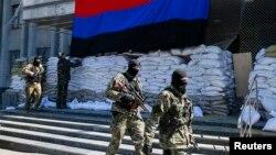 "Pro-Russian armed men walk past activists hanging up a ""Donetsk Republic"" flag outside the mayor's office in Slovyansk, eastern Ukraine, April 21, 2014."