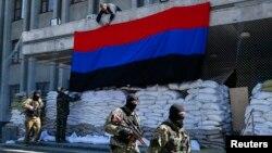 Các tay súng thân Nga đi ngang qua nơi các nhà hoạt động treo cờ 'Cộng hòa Donetsk' bên ngoài văn phòng thị trưởng ở Slovyansk, miền đông Ukraine, ngày 21/4/2014.