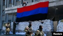 21일 친러시아 무장세력이 우크라이나 동부지역인 슬라뱐스크 청사에 도네츠크 공화국 국기를 매달고 있다.