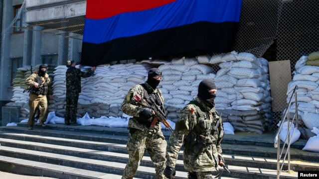 "Pro-Russian armed men walk past activists hanging up a ""Donetsk Republic"" flag outside the mayor's office in Slovyansk, eastern Ukraine, April 21, 2014."