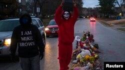 Dos individuos caminan en el lugar donde murió el joven Michael Brown en Ferguson, Missouri.