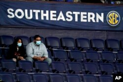Fans wear masks and sit in marked-off seats at an NCAA college basketball game in the Southeastern Conference tournament Wednesday, March 10, 2021, in Nashville, Tenn.