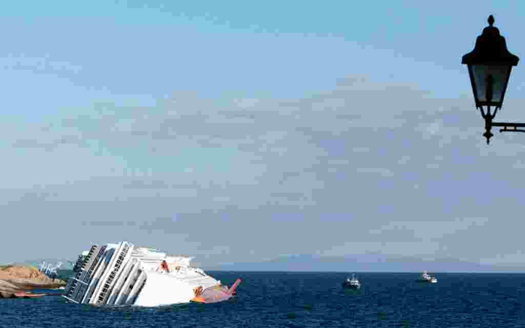 Kapal pesiar Costa Concordia masih terdampar di pesisir Pulau Giglio, Selasa, 17 Januari (AP).