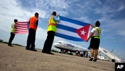 Airport workers receive the JetBlue flight 387 holding a United States, and Cuban national flag, on the airport tarmac in Santa Clara, Cuba, Aug. 31, 2016.