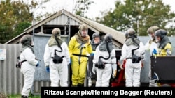 Employees from the Danish Veterinary and Food Administration and the Danish Emergency Management Agency in protective equipment are seen amid the coronavirus disease (COVID-19) outbreak at a mink farm in Gjoel, North Jutland, Denmark October 8, 2020.