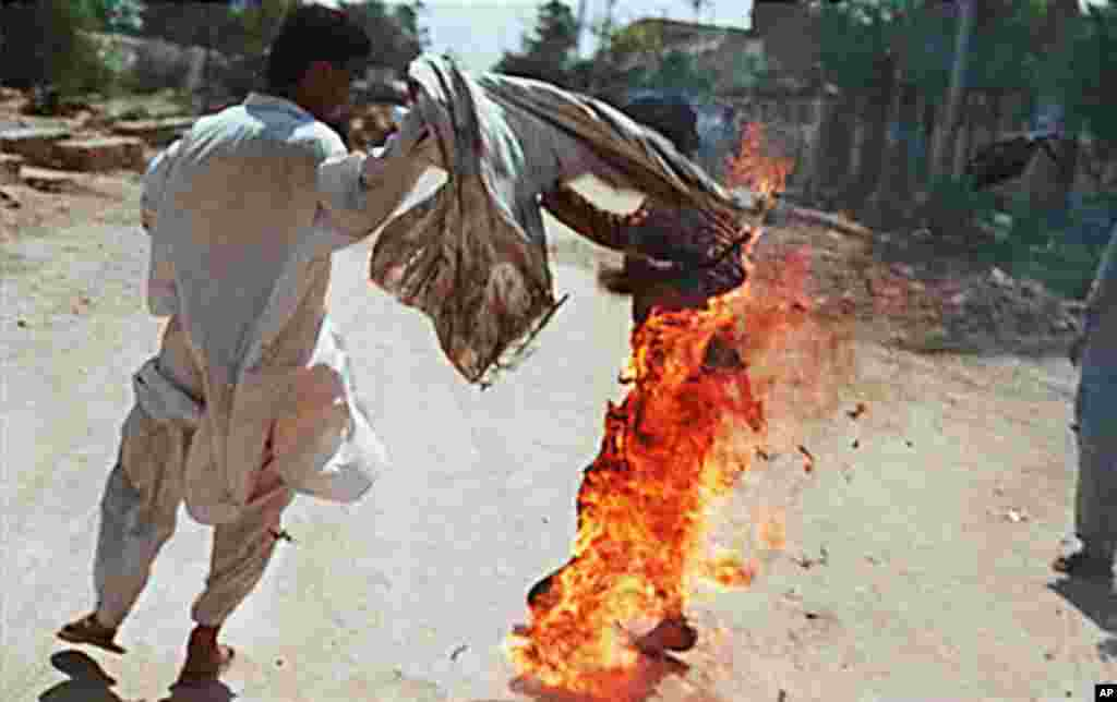 An unidentified man (L) tries to save 26 year-old Aaibunissa (R) who carried out a self-immolation along with another relative woman in front of the Hyderabad special terrorist courts in Karachi. The two women, Zaibunissa and Hakimzadi doused themselves