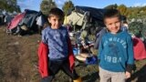 Two boys pose at an illegal improvised camp