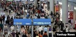 인천공항에서 탑승구를 찾아 이동하고 있는 여행객들.