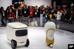 FILE - Attendees wave at Honda robotics concepts 3E-C18, left, and 3E-A18, at CES International, in Las Vegas, Nevada, Jan. 9, 2018.