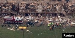 FILE - Police and rescue workers stand near a building which was destroyed in a massive explosion at a fertilizer plant in the town of West, near Waco, Texas, April 18, 2013.