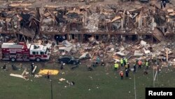 警察和救援人员站在被化肥厂爆炸而摧毁的大楼废墟旁