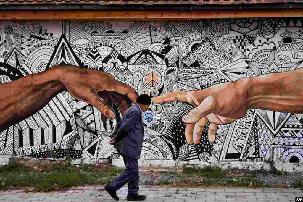 A pedestrian walks past a mural artwork painted on the wall of a house in the town of Ferizaj, Kosovo.