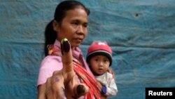 Seorang ibu sambil menggendong bayinya menunjukkan jarinya usai mencoblos di Bondowoso, Jawa Timur dalam pemilu 2014 (Foto Reuters/Sigit Pamungkas).