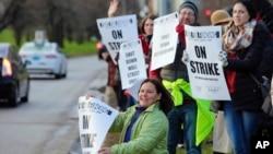 """Los manifestantes procedentes de diversas escuelas públicas de la ciudad, llevaban pancartas que decían """"En huelga"""" o """"Salva a nuestras escuelas""""."""