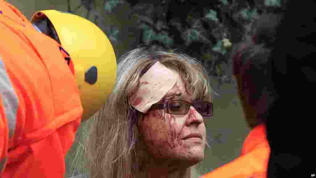 Paramedics help an injured woman after an explosion in Prague, April 29, 2013.