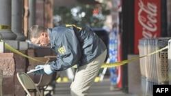 Một nhân viên F.B.I. thu thập thông tin tại hiện trường nơi dân biểu Gabrielle Giffords bị bắn bên ngoài một cửa hàng bán thực phẩm ở Tucson, Arizona, 10/1/2011