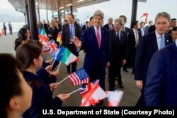 U.S. Secretary of State John Kerry greets school children as they arrive on Miyajima Island, Japan, as he and the other Group of Seven foreign ministers have a walking tour of the island amid the G-7 meetings, April 10, 2016.