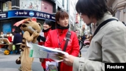 A Japanese tourist (R) speaks to a volunteer interpreter in Central Seoul April 8, 2013.