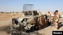 库尔德安全部队成员查看属于伊拉克安全部队的车辆残骸