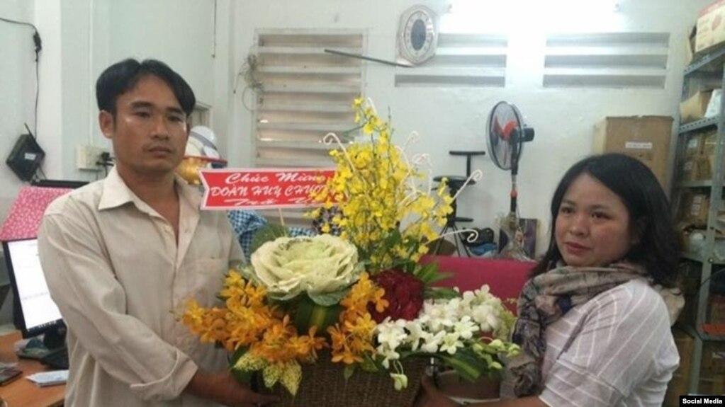 Đoàn Huy Chương (bên trái) nhận hoa chúc mừng từ Đỗ Thị Minh Hạnh, đại diện Phong Trào Lao động Việt, ngày 15/2/2017. (Facebook Phong Trào Lao động Việt).