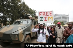 FILE: Euphoric crowds march on the streets of Harare, demanding the departure of President Robert Mugabe, Saturday Nov, 18, 2017. The military, which put Mugabe under house arrest, approved the demonstration.