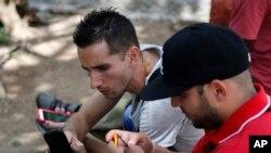 Orang-orang menggunakan smartphone untuk berselancar di Internet menggunakan hotspot Wi-Fi umum pertama di Havana, Kuba, 2 Juli 2015.