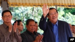Cambodia's Prime Minister Hun Sen waves on his arrival for a groundbreaking ceremony for a bridge over the Tonle Sap river, at Russey Keo village near Phnom Penh, Cambodia, Monday, Oct. 23, 2017. (AP Photo/Heng Sinith)