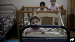 FILE - In this Aug. 15, 2018 file, photo, baby girls stand up in their cribs at Salhiya Orphanage, which now hosts foreign and Iraqi children of IS militants, in Baghdad, Iraq.