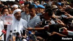 Pemimpin Front Pembela Islam (FPI), Muhammad Rizieq Shihab, berbicara kepada para wartawan di Mabes Polri menyusul pemanggilannya. Rizieq saat itu dipanggil polisi untuk ditanyai seputar klaimnya bahwa lembaran uang kertas baru bergambar simbol mirip lambang komunis palu dan arit, yang dilarang di Indonesia, Jakarta, 23 Januari 2018.