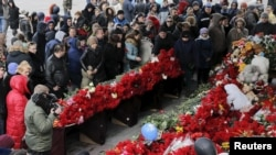 FILE - People are seen gathered paying tribute to the victims of crashed FlyDubai flight FZ981 outside the airport of Rostov-on-Don, Russia, March 20, 2016.