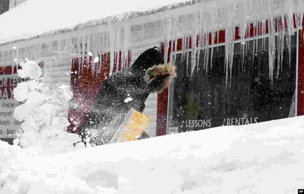 Resident Corbit Larson clears snow in front of his Centre Music store in Framingham, Massachusetts. A major winter storm that began on February 7 is still affecting parts of southern New England.