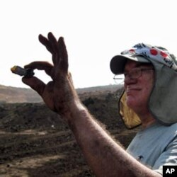 Paul Nascimbene holds up ancient amber found in India.