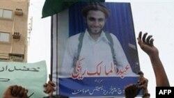Các nhà hoạt động Pakistan cầm hình thủ lãnh phiến quân Hồi giáo Sunni Abdolmalek Rigi trong cuộc biểu tình chống Iran tại Karachi