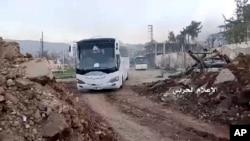 Esta foto tomada de un video de la prensa estatal siria muestra autobuses que transportan a combatientes de la oposición abandonando Zabadani, cerca de Damasco, Siria, el miércoles, 19 de abril de 2017, en dirección a Idlib, en el norte, en poder de los rebeldes.