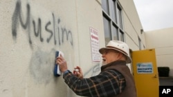 Tom Garing cleans up racist graffiti painted on the side of a mosque in what officials are calling an apparent hate crime, Feb. 1, 2017, in Roseville, Calif.