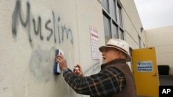 FILE - Tom Garing cleans up racist graffiti painted on the side of a mosque in what officials are calling an apparent hate crime, Feb. 1, 2017, in Roseville, Calif. (AP Photo/Rich Pedroncelli)