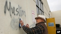 FILE - Tom Garing cleans up racist graffiti painted on the side of a an Islamic center in what officials are calling an apparent hate crime, Feb. 1, 2017, in Roseville, California. The Tarbiya Institute was spray-painted with a dozen obscene and racist slurs. Garing, a retiree who lives in the area and is not a member of the mosque, volunteered to help clean up.