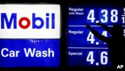 A gas station attendant raises gas prices on a display at Mobil gas station in Chicago, April 6, 2012.
