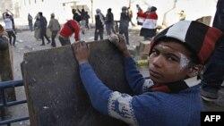Một cậu bé tìm chỗ tránh trong khi những người biểu tình ném đá vào lực lượng an ninh Ai Cập