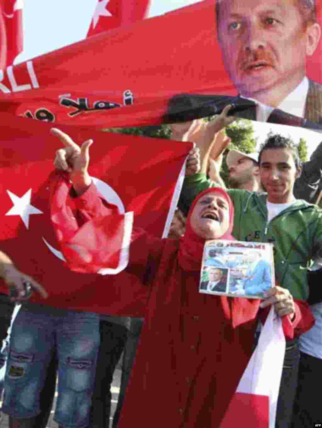 Supporters of Turkish Prime Minister Recep Tayyip Erdogan carry his pictures along Turkish flags as they gather outside Beirut International airport upon Erdogan's arrival in Lebanon, Wednesday, Nov. 24, 2010. (AP Photo/Bilal Hussein)